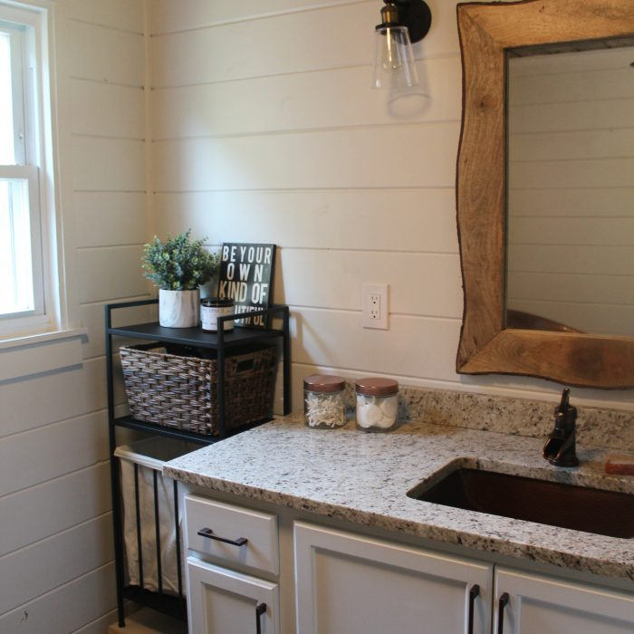 A modern farmhouse bathroom - with a copper tub, copper sink, wood plank ceiling, white shiplap walls, LVT flooring, and granite countertops.