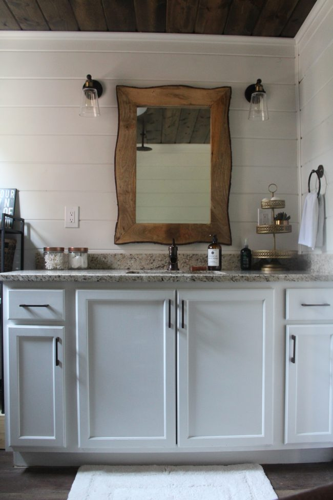 A modern farmhouse bathroom makeover - with a copper tub, copper sink, wood plank ceiling, white shiplap walls, LVT flooring, and granite counter tops.