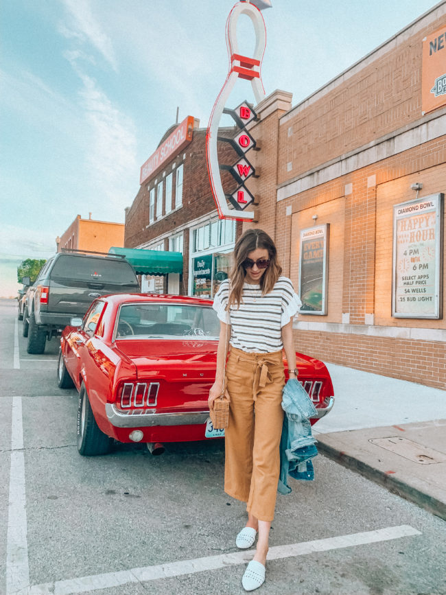 Striped ruffled top, mustard paperbag waist pants, and white mules outfit || Denim jacket outfit || Casual spring and summer style || What to do in Independence, Missouri - A guide to all the fun stuff! | Kansas City life, home, and style Blogger Megan Wilson shares a staycation trip to Independence, Missouri! #lovethesquare #staycation #visitmissouri