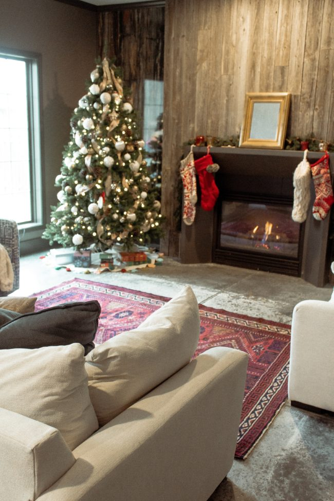A vintage area rug in our living room || Slowly but surely decorating our new home! || Kansas City life, home, and style blogger Megan Wilson shares a peek at a new rug in her home's living room // concrete floors, vintage area rug, Christmas tree, fireplace