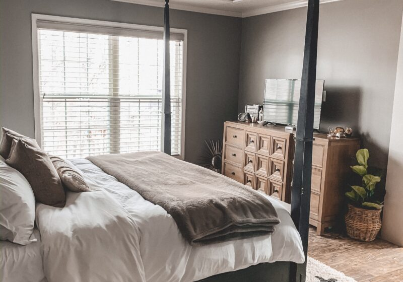 Black and white area rug in master bedroom, white bedding, black four poster bed || Neutral master bedroom design, plus the plans we have to change things up! Kansas City life, home, and style blogger Megan Wilson shares her master bedroom design plans and inspiration