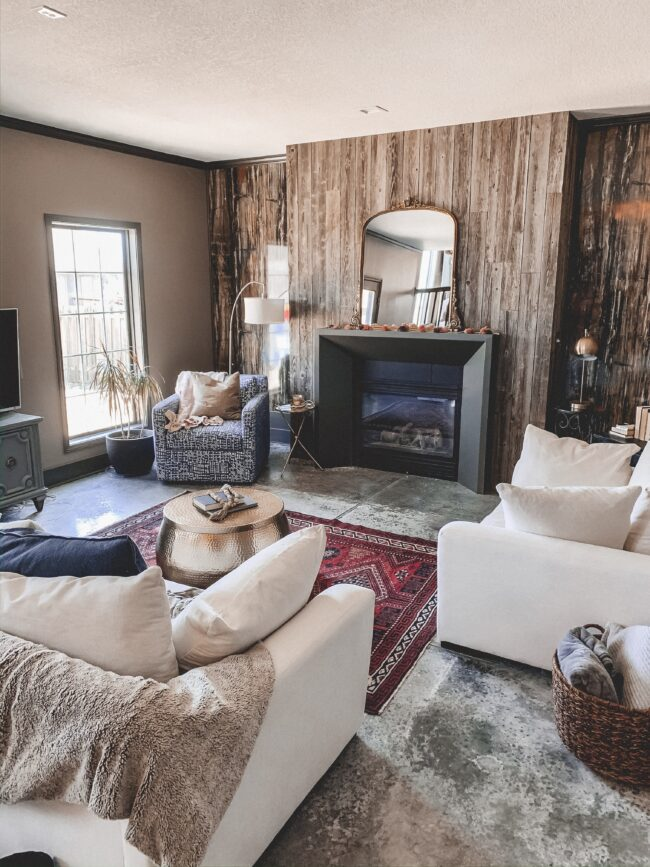 Gold Mirror over the Fireplace in the Living Room, vintage rug, black modern fireplace, white couch, wood planked fireplace wall || Kansas City life, home, and style blogger Megan Wilson shares a living room update