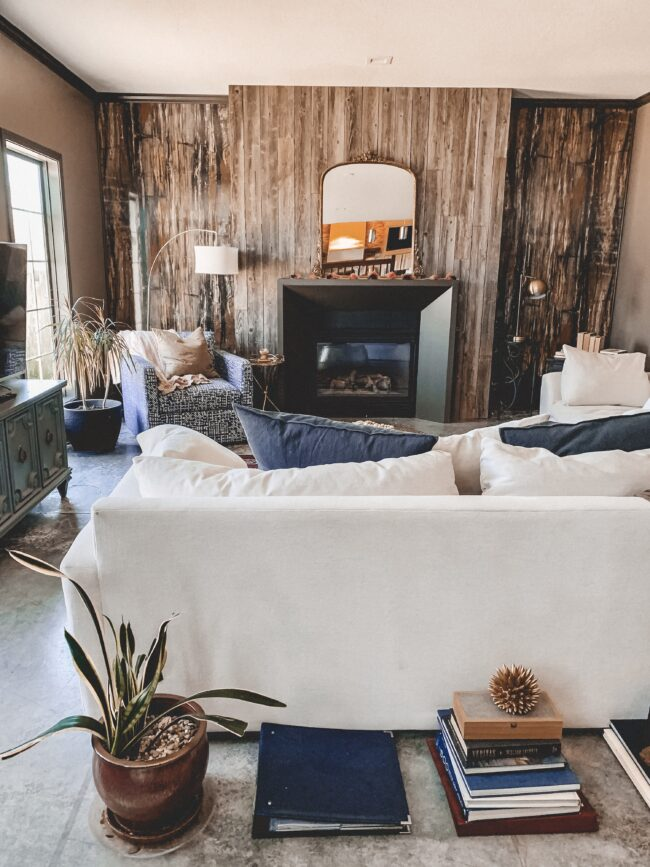 Gold Mirror over the Fireplace in the Living Room, black modern fireplace, navy throw pillows, white couch, wood planked fireplace wall || Kansas City life, home, and style blogger Megan Wilson shares a living room update