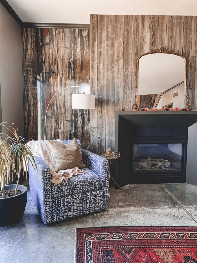Gold Mirror over the Fireplace in the Living Room, vintage rug, blue chair, black fireplace, wood planked fireplace wall || Kansas City life, home, and style blogger Megan Wilson shares a living room update