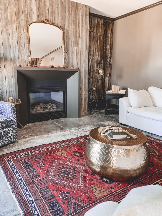 Gold Mirror over the Fireplace in the Living Room, gold hammered metal coffee table, black modern fireplace, white couch, wood planked fireplace wall || Kansas City life, home, and style blogger Megan Wilson shares a living room update