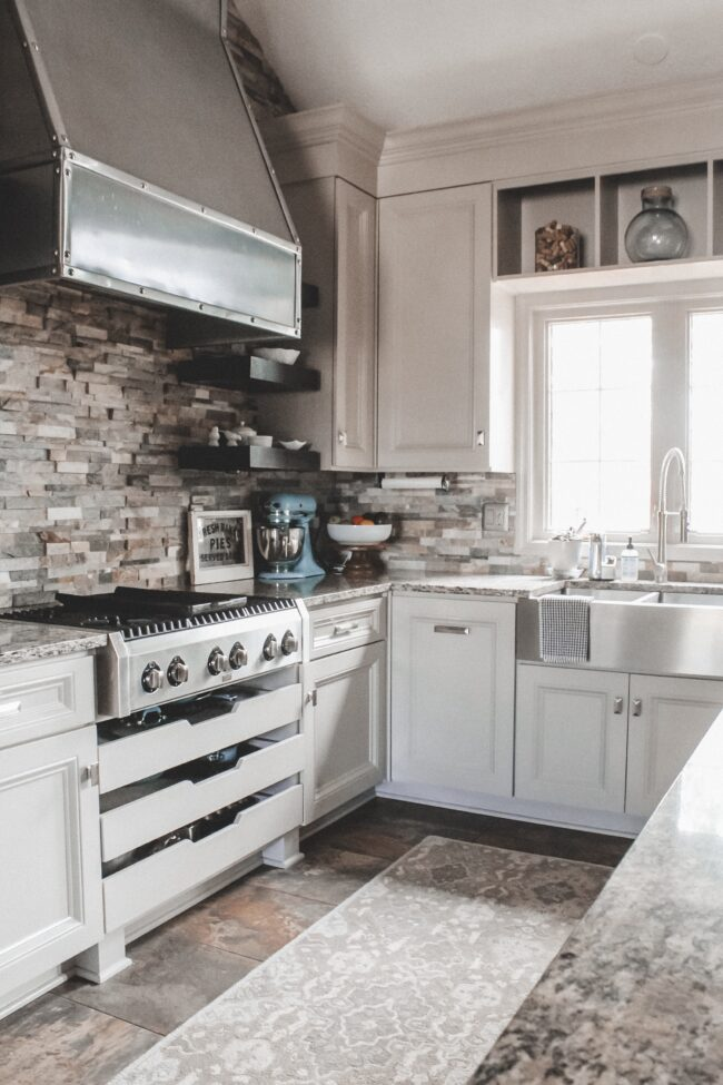 Home Tour: our rustic meets modern kitchen! Kansas City life, home, and style blogger Megan Wilson shares a tour of her new home's kitchen with stone backsplash, stainless range hood, granite and wood countertops, metal and wood accents, stainless farmhouse kitchen sink, and open shelves.