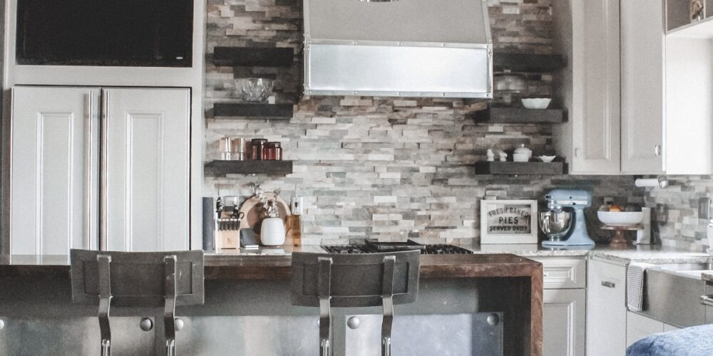 Home Tour: our rustic meets modern kitchen! Kansas City life, home, and style blogger Megan Wilson shares a tour of her new home's kitchen with pendant lights over the island, stainless range hood, stone backsplash, granite and wood countertops, metal and wood accents, stainless farmhouse kitchen sink, and open shelves.