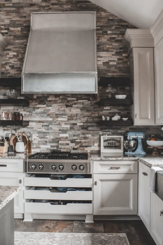Home Tour: our rustic meets modern kitchen! Kansas City life, home, and style blogger Megan Wilson shares a tour of her new home's kitchen with stone backsplash, granite and wood countertops, stainless range hood, metal and wood accents, stainless farmhouse kitchen sink, and open shelves.