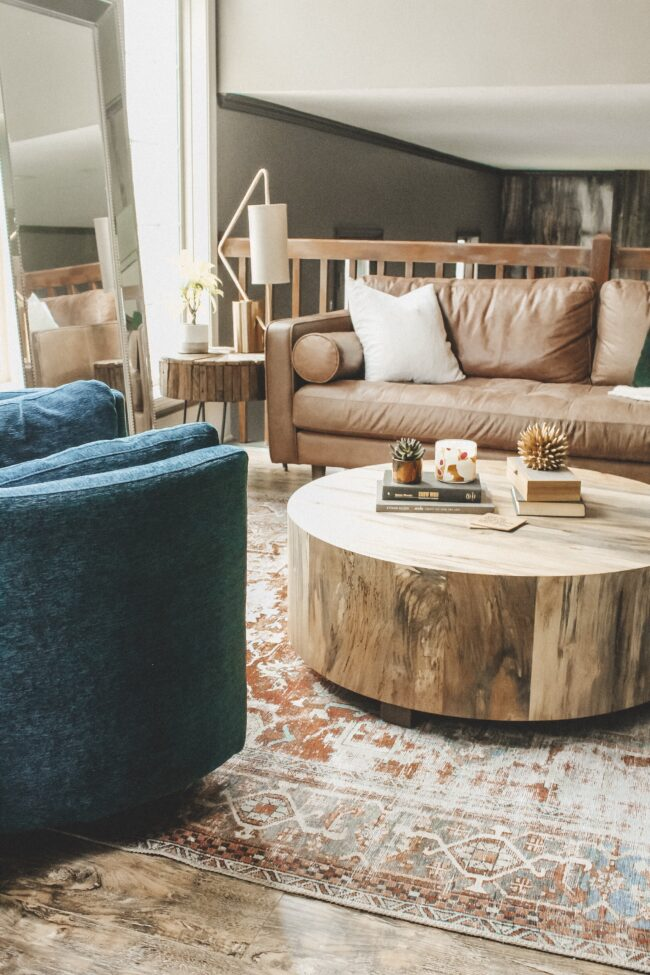 Home Tour: our living room makeover!! Kansas City life, home, and style blogger Megan Wilson shares how she refreshed her living room with matching recliners, a turkish-inspired area rug, round coffee table, distressed wood side table, unique table lamp, and leather couch