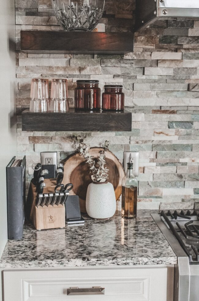 Home Tour: our rustic meets modern kitchen! Kansas City life, home, and style blogger Megan Wilson shares a tour of her new home's kitchen with stone backsplash, granite and wood countertops, metal and wood accents, stainless farmhouse kitchen sink, and open shelves.