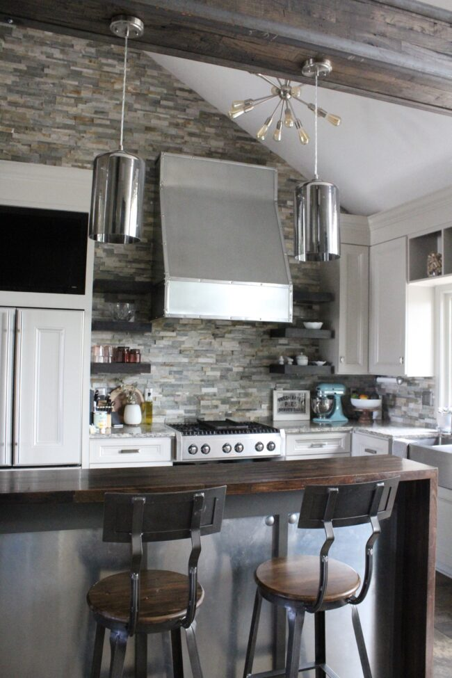 Rustic meets modern kitchen, stone backsplash, stainless steel range hood || Kitchen inspiration || Kansas City life, home, and style blogger Megan Wilson shares a tour of her home, recently featured in Kansas City magazine
