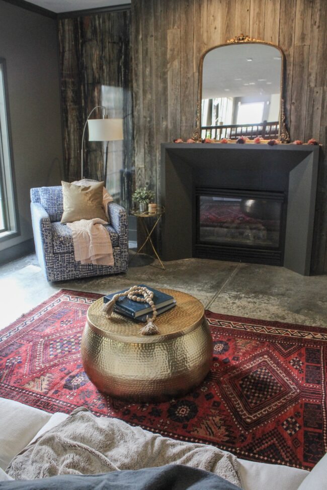 Vintage rug, gold coffee table, wood plank fireplace wall || Living Room || Kansas City life, home, and style blogger Megan Wilson shares a tour of her home, recently featured in Kansas City magazine